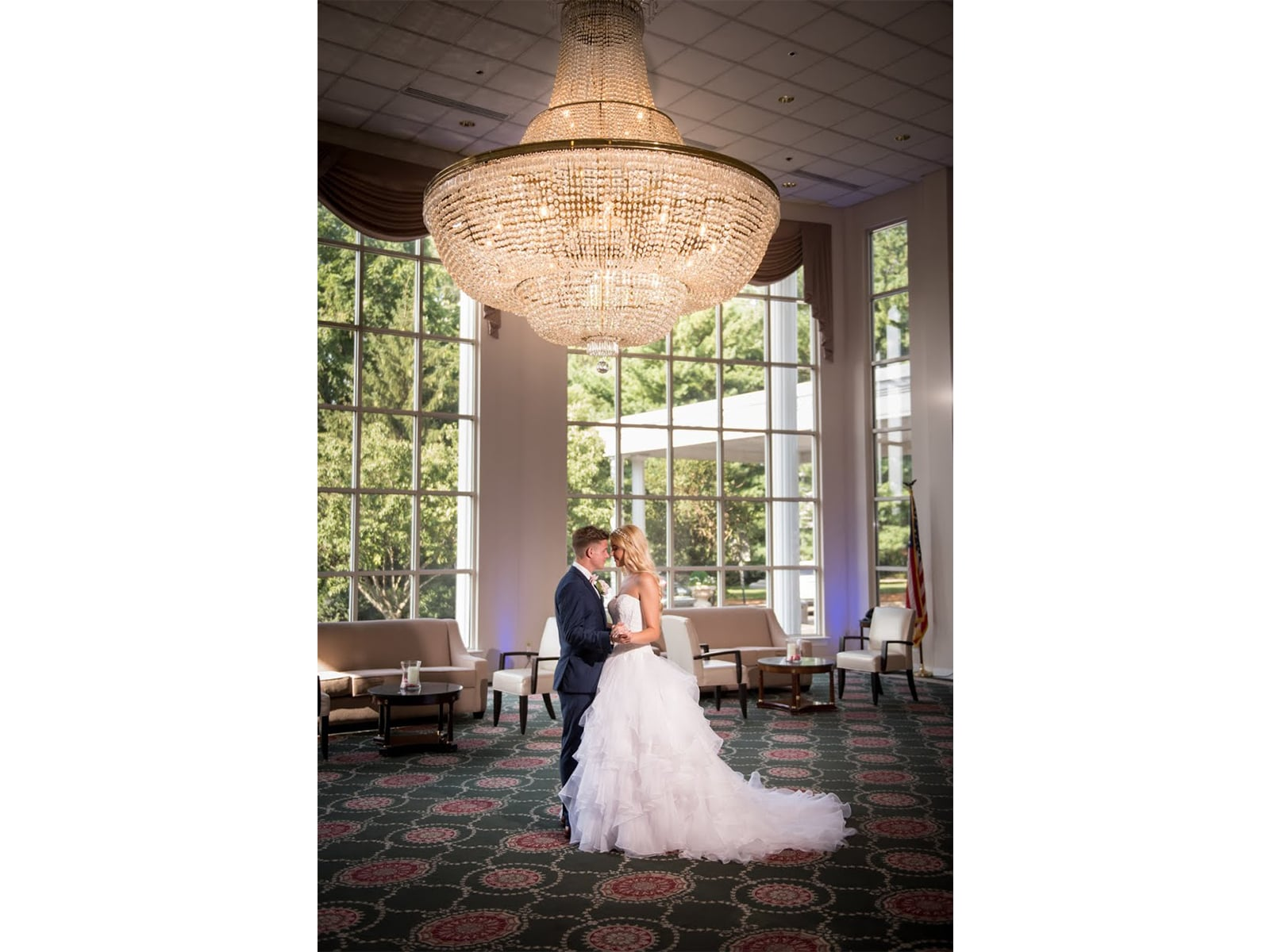Husband and wife dancing under a chandelier at a Presidential Catering wedding.